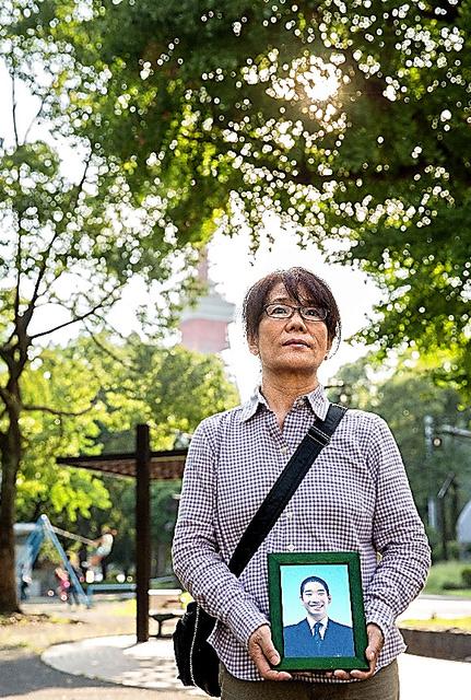 市川大輔さんが子どもの頃からよく訪れていた芝公園で遺影を手にする母正子さん=東京都港区、鬼室黎撮影
