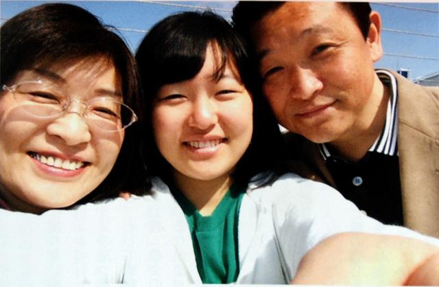 父光夫さんと母良子さんに囲まれる伊藤琴美さん=2014年4月撮影、遺族提供