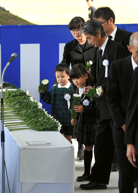 御嶽山噴火災害犠牲者追悼式で、祭壇に献花する遺族=27日午後0時46分、長野県王滝村の松原スポーツ公園(代表撮影)