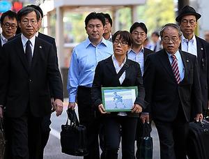 市川大輔さんの遺影を手に東京地裁に向かう母の正子さん(前列中央)=29日午前9時33分、東京・霞が関、林敏行撮影