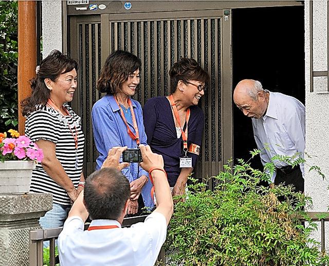足立区東保木間(ほぎま)町会では13人のボランティアが7人の高齢者を見守る。区職員(手前)の求めに応じ、訪問の手順を見せてくれた=5月、仙波理撮影