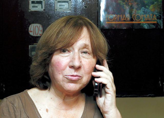 ベラルーシ・ミンスクで8日、自宅を出て電話で話す作家のスベトラーナ・アレクシエービッチさん=ロイター