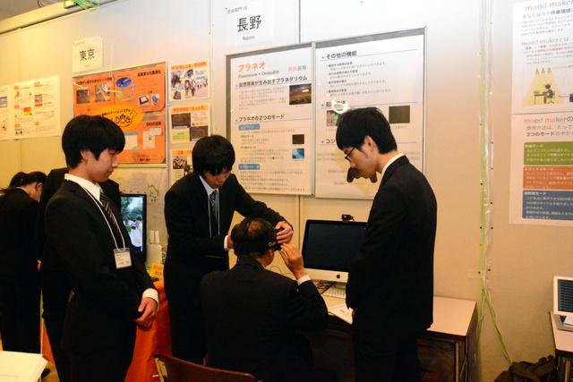 長野高専の学生から作品の説明を受ける来場者=長野市若里のホクト文化ホール