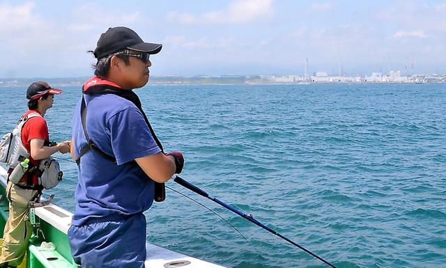 福島第一原発(右奥)を望みながら、調査用の魚を求めて釣りをする「うみラボ」のメンバー=福島県沖