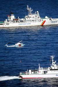 訓練で救助者を巡視船からつり上げる海上保安庁のヘリコプター。後方は韓国の海洋警備安全本部の警備艦=14日午前、長崎県・対馬沖、朝日新聞社ヘリから、森下東樹撮影