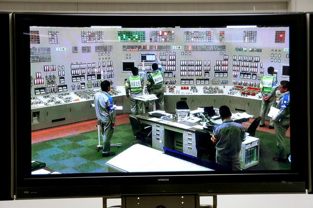 九州電力川内原発の中央制御室で2号機の原子炉の起動操作をする運転員ら。薩摩川内市内にある九電施設で、ライブ映像が報道陣に公開された=15日午前、鹿児島県薩摩川内市