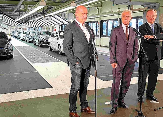 VW本社工場内で記者会見するマティアス・ミュラー最高経営責任者(中央)やニーダーザクセン州のシュテファン・ワイル首相(右)ら=21日、ウォルフスブルク
