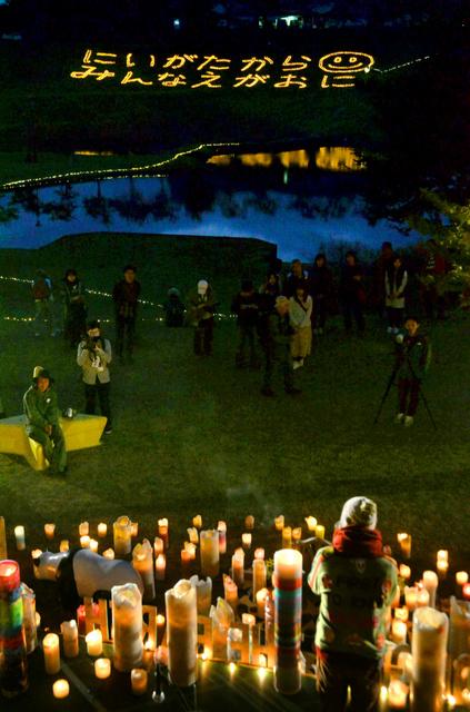 ろうそく3千本に火をともし、「にいがたからみんなえがおに」という文字を描いた=長岡市川口中山の川口運動公園