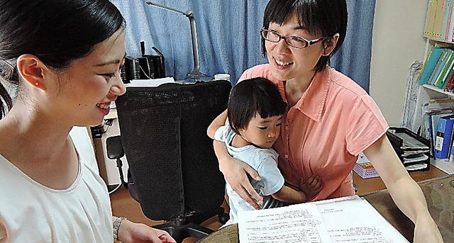 娘を抱きながら、大学生(左)と打ち合わせをする熊本市議の緒方夕佳さん=熊本市東区