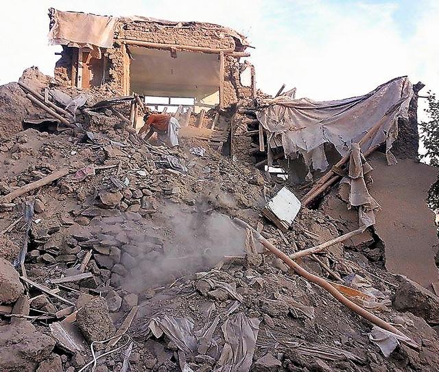 アフガニスタン北東部で26日、地震で壊れた建物のがれきを掘る男性