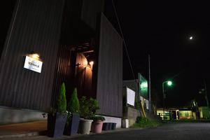 午後9時前、人影の途絶えた駅舎(奥)。バー(手前)では客の談笑が続いていた=千葉県銚子市野尻町