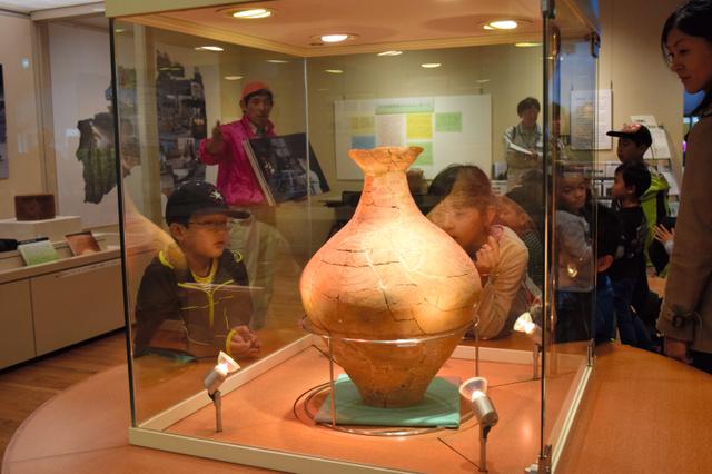 「Jヴィレッジ」で発掘された弥生土器を、解説を聞きながら眺める子どもたち=白河市の県文化財センターまほろん