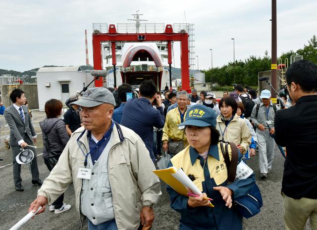 フェリーを下り、バスに向かう伊方町からの防災訓練参加者ら=9日午前11時52分、大分市の佐賀関港、菊地洋行撮影