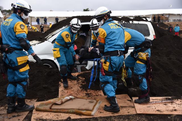土砂に埋まった車内に閉じ込められた人を救助する参加者ら=山梨県の陸上自衛隊北富士演習場