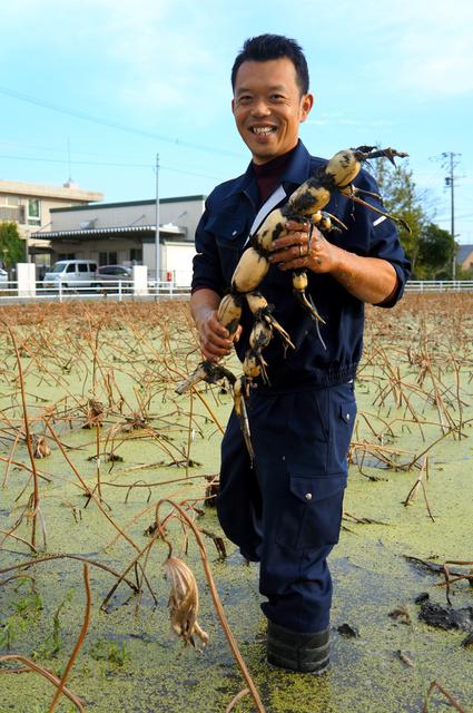 水を張った田でレンコンを手にする川上大介さん=熊本市