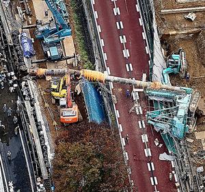 外環道脇で倒れた工事用の重機=21日午後3時28分、東京都練馬区、本社ヘリから、堀英治撮影