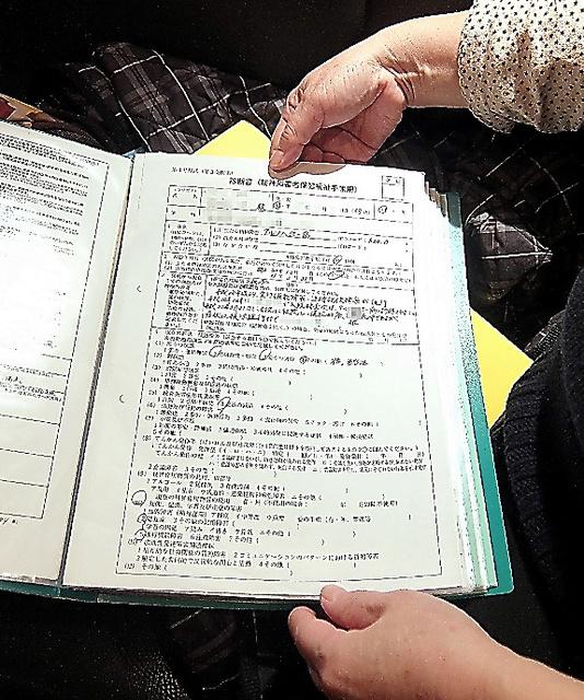 夫の障害者手帳などを申請したときの記録を手にする東京都の女性(名前や住所にモザイクをかけています)