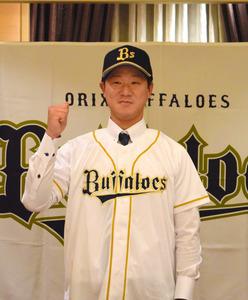 仮契約後、オリックスバファローズのユニホームに袖を通した赤間謙投手=東京都内のホテル