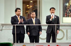 大阪市長選の敗北から一夜明け、街頭であいさつする柳本顕氏(右)と選対本部長の高野伸生・自民市議(中央)=23日午前、大阪市中央区
