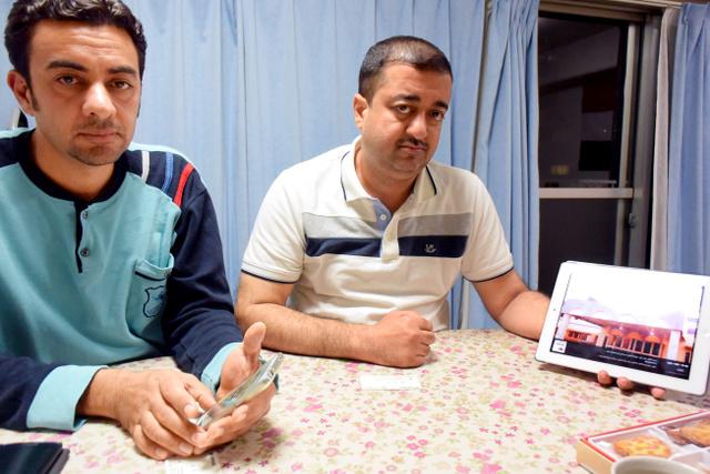タブレット端末で、ラマディの病院の写真を見せるアルカンさん(右)とバッシムさん=名古屋市中区