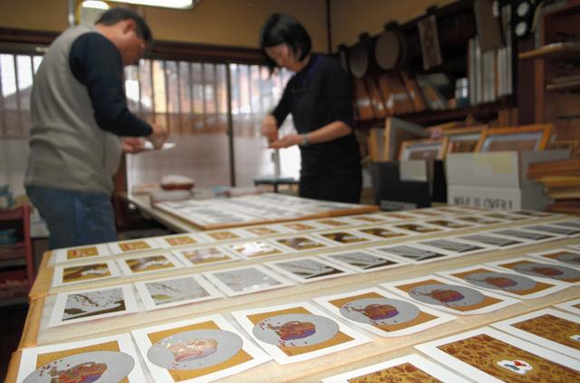 金や銀の粉を重ね、鮮やかな年賀状ができあがっていく=会津若松市馬場町