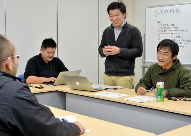 会議に向けて笑顔で打ち合わせをする平山勉さん(右)ら=広野町