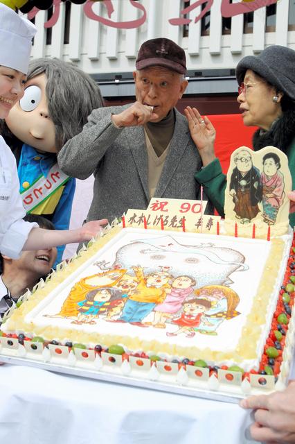 リニューアルオープンした水木しげる記念館の前で卒寿祝いのケーキを贈られる水木さんと妻の布枝さん(右)=2012年、境港市本町