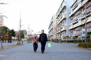 手をつないで団地を歩く、村上守さん(右)と京子さん=埼玉県三郷市、川村直子撮影