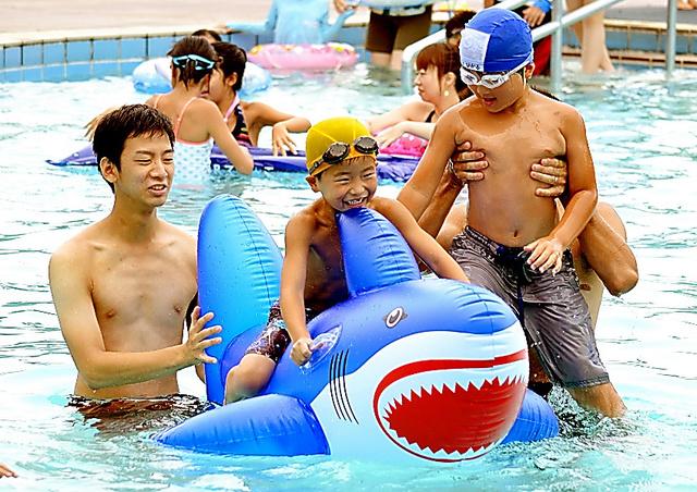 東京の西多摩地域の市民グループに招かれた福島の子どもたち。屋外でプール遊びを楽しんだ=今年8月、東京都の国営昭和記念公園