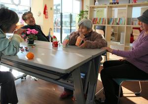 連載のプロローグに登場した認知症の村上京子さん(中央)は、地域の交流スペースの人気者だ。夫の守さん(左)、ボランティアの女性らと穏やかな時を過ごす=埼玉県三郷市、川村直子撮影