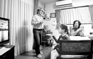 食後にカラオケを楽しむ松浦宏昌さん(左)と俊子さん。曲の歌い出しを「はい、ここから!」と孫に教えられ「参っちゃうなぁ」と額を押さえた=東京都町田市、川村直子撮影