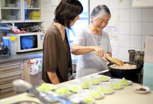 グループホームで夕食作りを手伝う飛田友子さん(右)。おいしそう、と娘が傍らで声をかけると笑みがこぼれた=東京都世田谷区、川村直子撮影