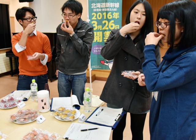 北海道新幹線開業に合わせて売り出す菓子の試食をする室蘭工大の学生ら=室蘭市