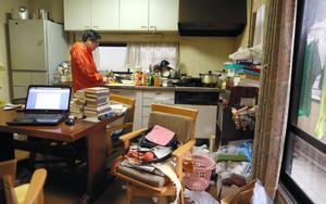 台所で、母が食べやすいよう柿を小さく切る冨井淑夫さん。ここで原稿も書く=京都市、川村直子撮影