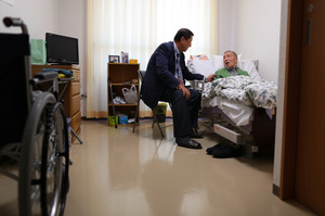 介護施設で暮らす筑紫さん(右)。田中さんが声をかけると表情が和らいだ=埼玉県狭山市、川村直子撮影