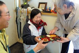 デイサービスのスタッフと一緒に、女性宅へお弁当を届ける国井香さん(中央)=東京都練馬区、川村直子撮影