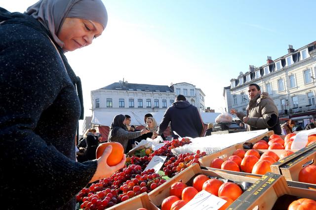 モランベーク地区の広場で開かれるマルシェ(市場)は大勢の買い物客でにぎわう。奥はテロ実行犯とされる兄弟が住んでいたというアパート=3日午後、ブリュッセル、遠藤啓生撮影