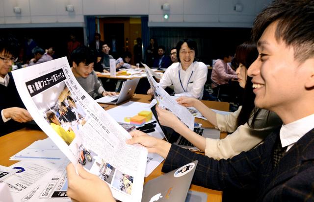 途中経過をまとめた「号外」を手にする参加者たち=6日午前、東京都港区、角野貴之撮影