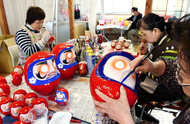 双葉ダルマの絵付けをする双葉町の農協女性部の人たち。ダルマの大きさは高さ10~35センチの12種類ある=8日、福島県いわき市、福留庸友撮影