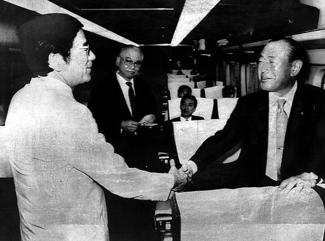 前年の衆院選で対決した田中角栄元首相と上越新幹線の車中で鉢合わせし、握手をした=1984年6月6日