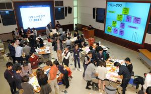 テーブルごとにグループに分かれ、意見を出し合う参加者ら=6日午前、東京都港区、角野貴之撮影