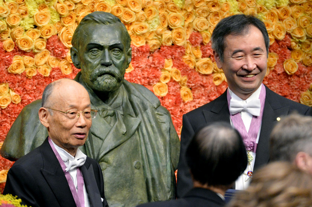10日、ストックホルムで行われたノーベル賞の授賞式後、アルフレッド・ノーベルの胸像前に立つ大村智さん(左)と梶田隆章さん=ロイター