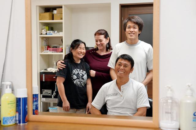 横田浩さん(右上)と浩子さん(左)夫妻が再建した理髪店を訪れた、伊藤ヒロさん(右下)とシンシア・ホワイトさん夫妻。伊藤さんは髪を切ってもらいながら近況をきく=2日午後、宮城県東松島市、福留庸友撮影