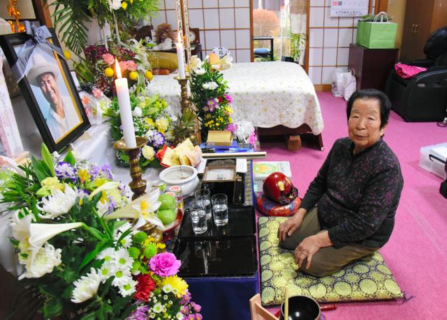 松本茂さんの遺影が飾られた祭壇の前に座る、妻のるいさん=大潟村