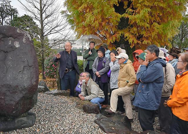 五日市憲法草案の条文の抜粋が刻まれている石碑前で、ツアー参加者に説明する鈴木富雄さん(左端)=東京都あきる野市