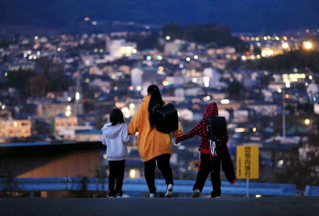 小学校からの帰り道、姉妹は母の手をぎゅっと握った=18日、長野県、内田光撮影