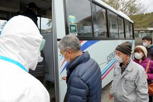 警察官の誘導で鹿児島市へ向かうバスに乗り込む住民=薩摩川内市高城町