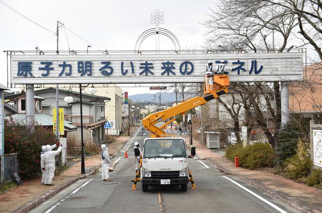 看板から文字を外す作業員たち=21日午前10時48分、福島県双葉町、福留庸友撮影