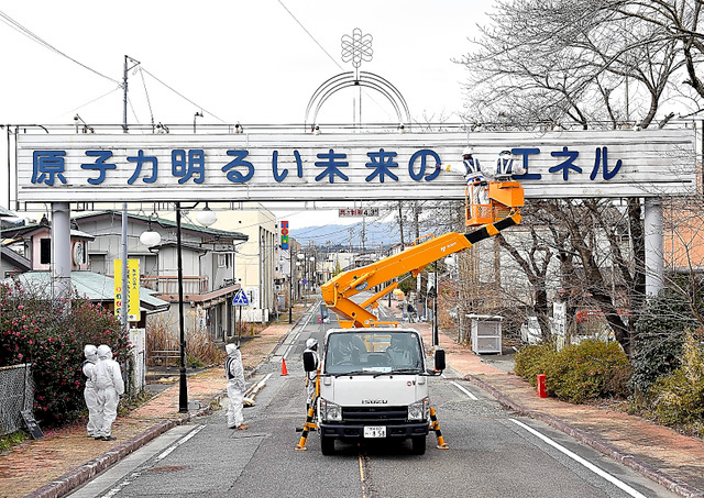 Workers take down letters of a signboard promoting nuclear energy in Futaba, Fukushima Prefecture, on Dec. 21. (Yosuke Fukudome)◇看板から文字を外す作業員たち=21日午前10時48分、福島県双葉町、福留庸友撮影