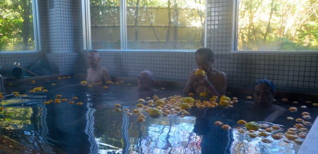 ユズが浮かべられた温泉を楽しむ入浴客=鹿児島市若葉町の芦刈温泉